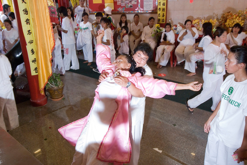 A female medium collapses after exiting a trance in the Phuket Vegetarian Festival Street Procession, Phuket Town, Thailand.....** The Phuket Vegetarian Festival celebrates the beginning of Taoist Lent, when devout Chinese abstain from eating all meat and other vices.  The festival takes place on the first 9 days of the 9th lunar month of the Chinese calendar.  Everyone dresses in white and shopkeepers set up small alters with offerings of incense, flowers, candles, fruit, and 9 cups of tea to the 9 emperor deities honored by the festival. ....Mediums bring the 9 gods to earth entering a trance state and piercing themselves with all kinds of objects, climbing knife ladders, and walking on hot coals.  The mediums participate in daily processions through town where they stop at the store front alters, drink one of the 9 cups of tea, and offer blessings to the merchants.  The shopkeepers stand in prayer like fashion respecting the mediums that are temporarily possessed by the deity.  The self torture is done to shift evil from individuals to the mediums and bring the community good luck.....Young men carry alters of the deity images though town which culminates at central locations where merchants cover them with huge strands of firecrackers and larger explosives.  The louder and longer blasts are best to drive away evil spirits.  The experience is deafening and engulfs the men and alters in a painful barrage of fire and smoke.  ....Chinese tour groups come to witness since there is no record of this type celebration of Taoist Lent in China.  The festival is believed to have started when a Chinese theatre troupe fell ill for failing to honor the 9 emperor gods of Taoism.  They were quickly cured when they adhered to the 9 day ritual now held each year promoting inner peace, brightness, and proper hygiene.  ..