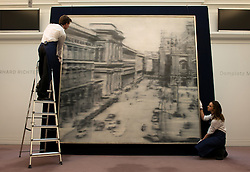 © Licensed to London News Pictures. 12/04/2013. London, UK. Gallery assistants mount the German artist Gerhard Richter's 'Domplatz, Mailand' painting with an estimated value of between 30 - 40 million USD for the upcoming New York auctions. Highlights from Sotheby's New York auctions of Impressionist and Modern Art and Contemporary Art will be exhibited to the public from 12-16 April at  Sotheby's London New Bond Street galleries. Photo credit : Peter Kollanyi/LNP