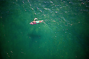 Aerial view of surfer paddling on clear green sea, calm water