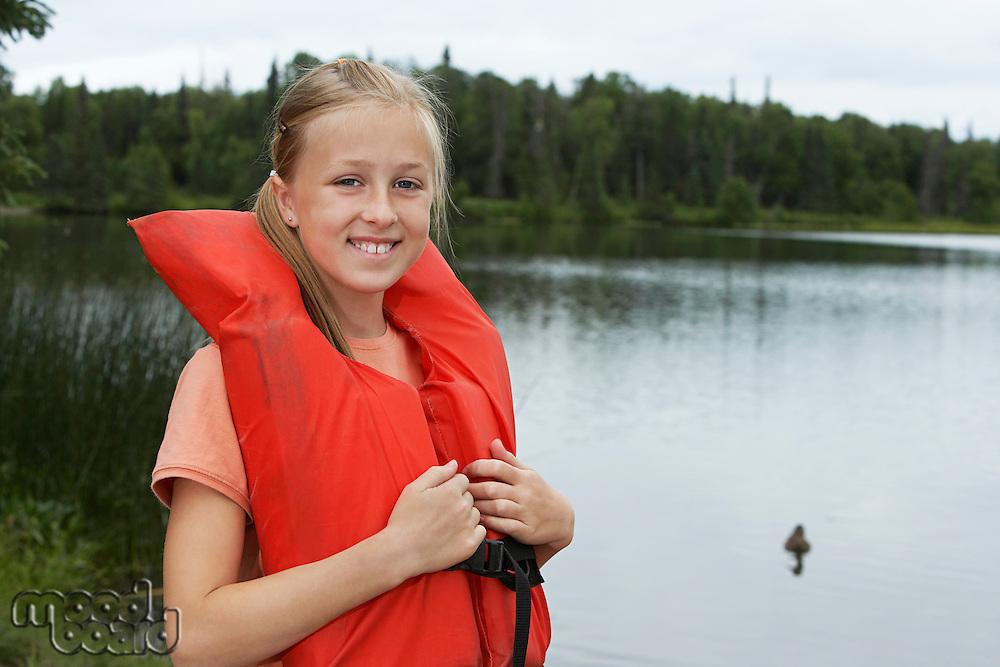 USA, Alaska, teenage girl wearing life jacket by lake, portrait