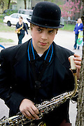 Musician age 18 in bowler hat holding a saxophone. MayDay Parade and Festival. Minneapolis Minnesota USA
