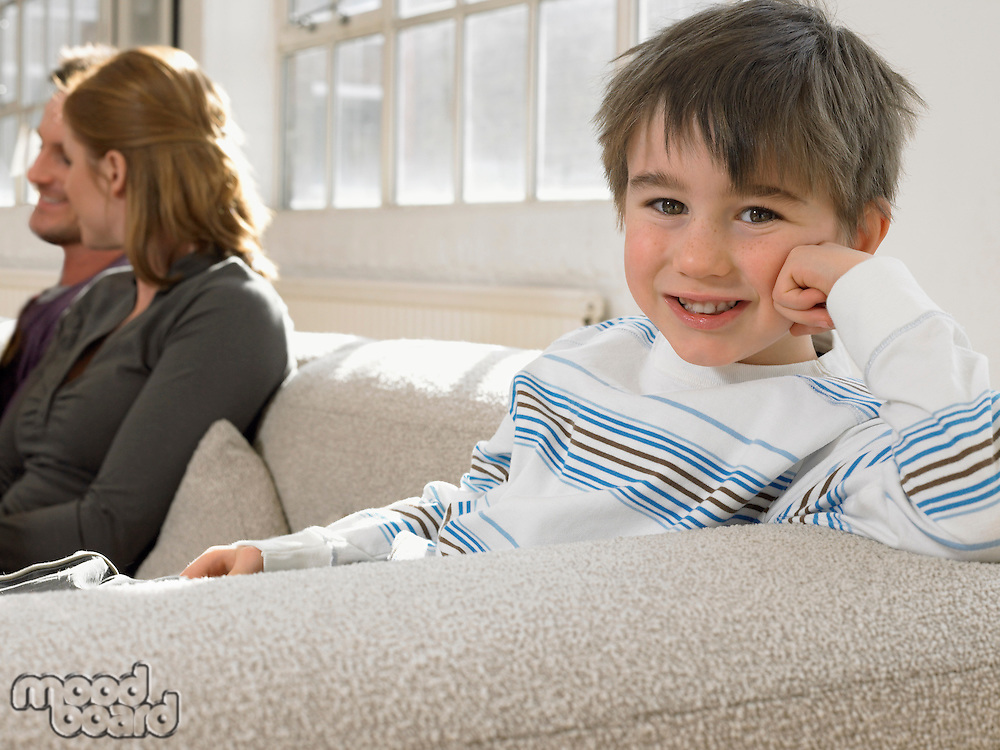 Boy (3-6) with parents on couch smiling (portrait)