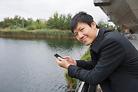 Portrait of happy businessman with cell phone leaning on bridge railing