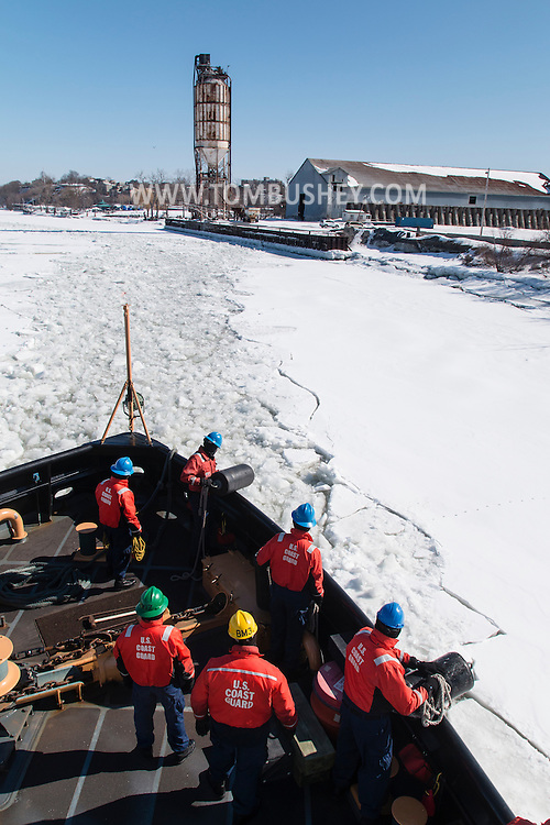 Crew members of the United States Coast Guard cutter Sturgeon Bay prepare to dock at a pier in Hudson, New York. The Sturgeon Bay was breaking ice in the shipping channel in the Hudson River.