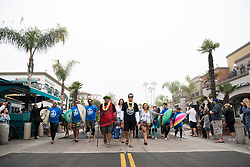 Jun 20, 2017 - Huntington Beach, California, U.S. - Local surfing legend BRETT SIMPSON (center, yellow shirt black hat) and some of the nearly 600 surfers cross Pacific Coast Highway at Main Street in downtown Huntington Beach Tuesday morning as they head for the ocean to create the world's largest paddle out ''Circle of Honor'' in Huntington Beach Tuesday morning. (Credit Image: © Pat Nolan/A-Frame/ZUMAPRESS.com)