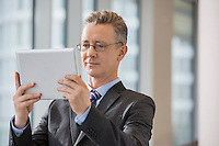 Businessman looking at digital tablet in office