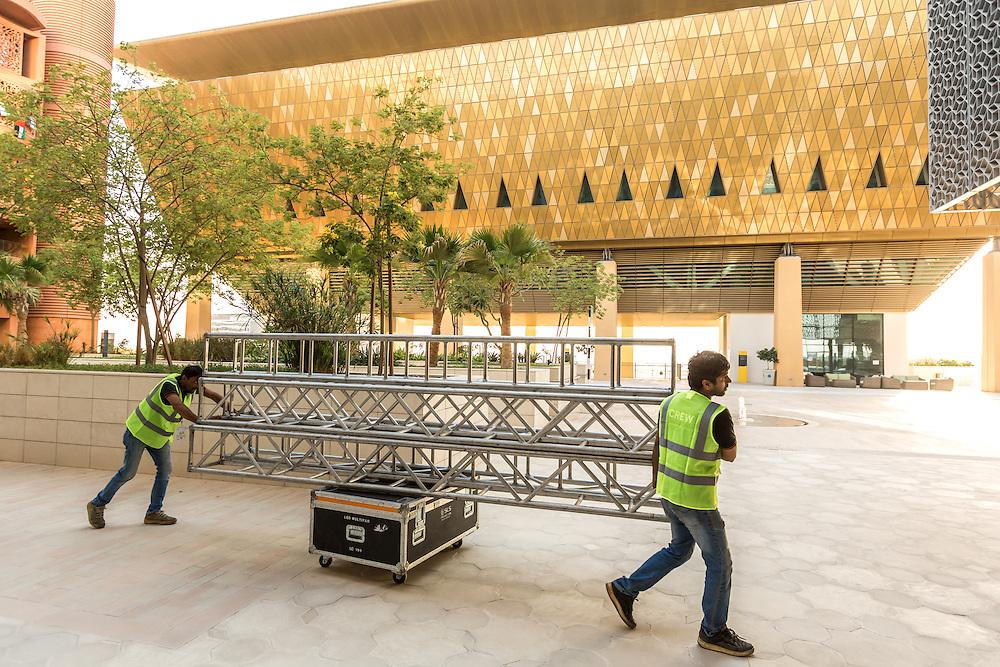 ABU DHABI, EMIRATS ARABES UNIS - 19 JANVIER 2016: Deux travailleurs s'affairent devant le complexe sportif de Masdar City en vue des animations du 'Abu Dhabi Sustainability Week'.