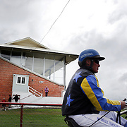 A horse and rider head for the parade ring past the grandstand during the Winton Harness Racing Club Race meeting at the Central Southland Raceway, WInton, Southland, New Zealand. 10th February 2012. Photo Tim Clayton