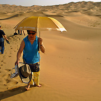 Some Chinese tourist take a walk trough Jin Sha Wan Golden Sand Bay desert close to the Wu Hai industrial city in to the Inner Mongolia Autonomous region. Every Year thousands of Tourist came from all around the country to spend their summer vacations in this lands. Aug-22-2006/ Photo: Stringer