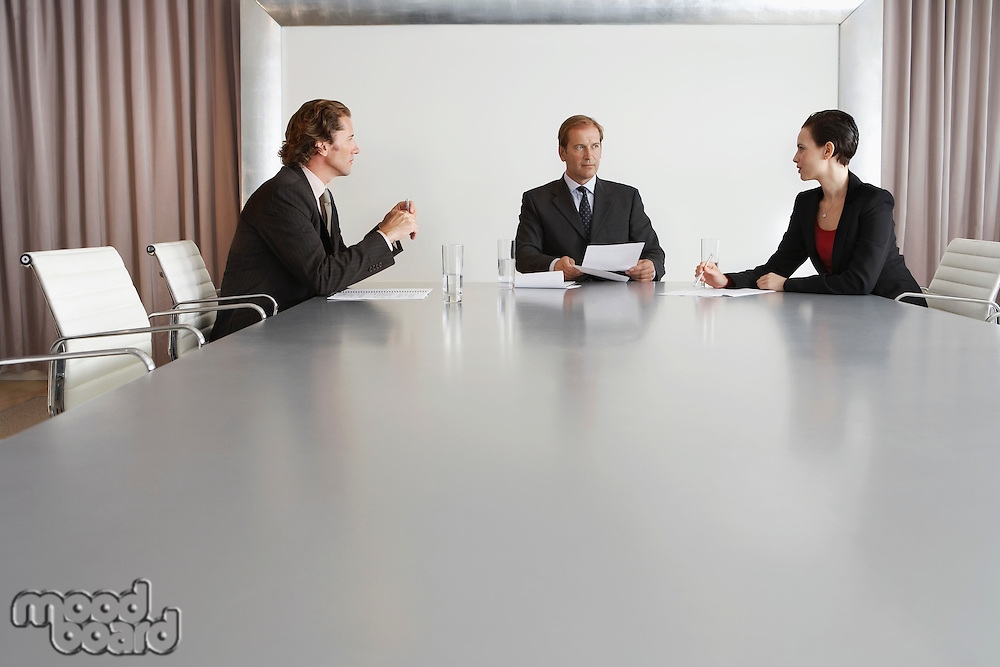 Three Businesspeople Meeting in Conference Room