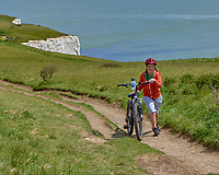 Walking a bicycle on a trail above the White Cliffs of Dover, England.