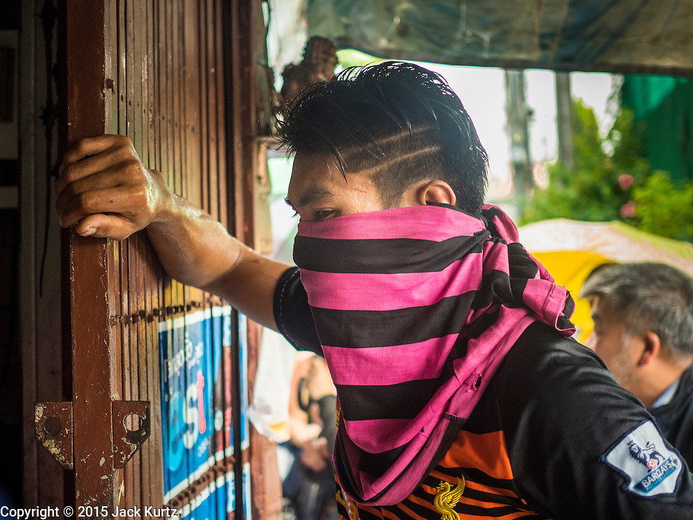 10 SEPTEMBER 2015 - BANGKOK, THAILAND:  A demolition worker gets ready to dismantle Chaiyasit Kittiwanitchapant's home. Authorities started to destroy 54 homes in front of Wat Kalayanamit, a historic Buddhist temple on the Chao Phraya River in the Thonburi section of Bangkok. Government officials, protected by police, seized the house of Chaiyasit Kittiwanitchapant, a Kanlayanamit community leader, who has led protests against the temple's abbot for trying to evict community members whose houses are located around the temple. Work crews went into Chaiyasit's home and took it apart piece by piece. The abbot of the temple said he was evicting the residents, who have lived on the temple grounds for generations, because their homes are unsafe and because he wants to improve the temple grounds. The evictions are a part of a Bangkok trend, especially along the Chao Phraya River and BTS light rail lines, of low income people being evicted from their long time homes to make way for urban renewal.    PHOTO BY JACK KURTZ