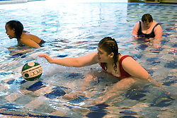 Day service users with learning disability playing with a ball in the water at a local swimming pool,