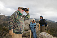 Senior man using binoculars in mountains