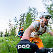 Andrew Whiteford (Blue Jersey) and Jay Goodrich (Orange Shorts) ride the Phillips Ridge Trail during peak wildflower season near Jackson, Wyoming.