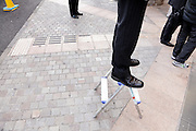 businessmen standing around with one standing on a stepladder