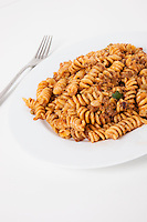 Spicy twisted pasta in plate over white background