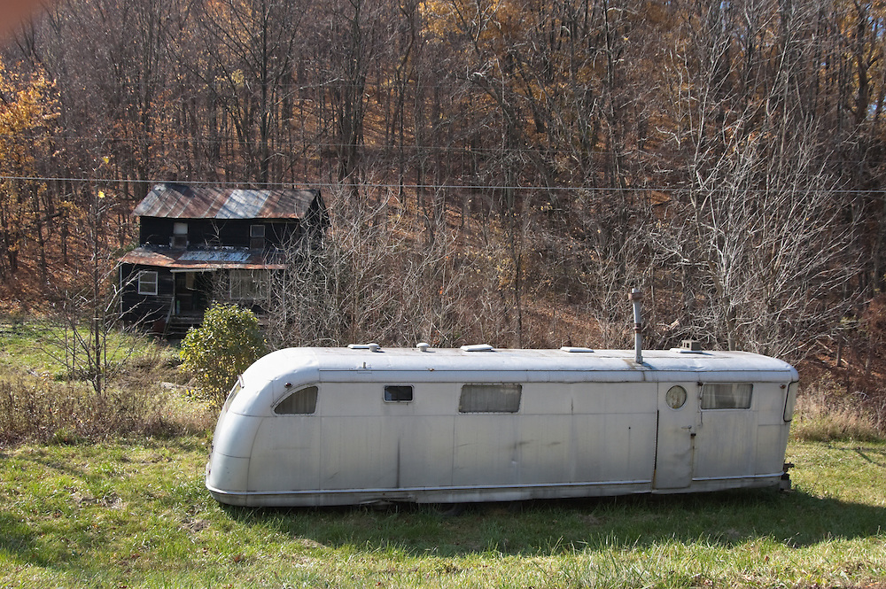Picture of unpainted weathered shack and silver mobile home trailer, abandoned, old, worn, and dented, hillbilly heaven in rustic backwoods Appalachia.