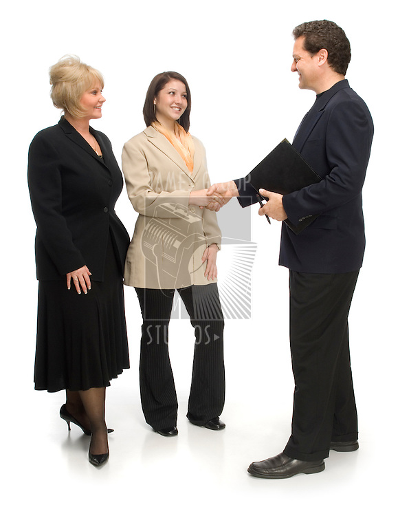 Two woman and one man dressed in business attire shaking hands on white