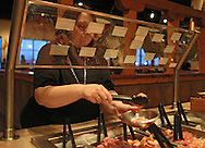 Julie Penrod prepares her dish at Genghis Grill, 2230 Edgewood Road SW, in Cedar Rapids on Thursday evening, March 1, 2012. Penrod is eating at Genghis Grill every evening for 60 days as a Health Kwest Khantestant. (Stephen Mally/Freelance)