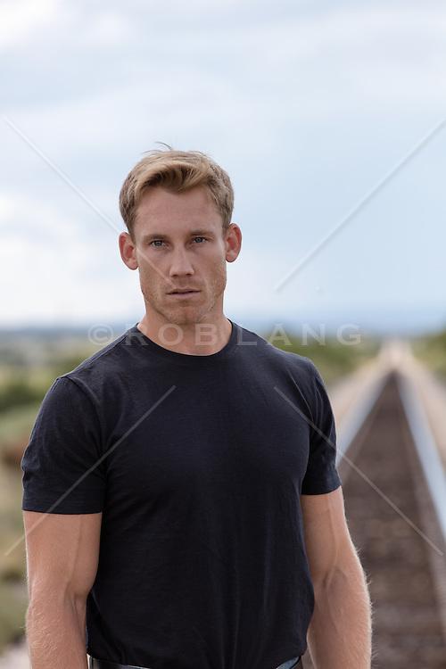 hot man in a black tee shirt on railroad tracks