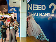 "23 AUGUST 2013 - BANGKOK, THAILAND:    Tourists line up at a TMB Exchange Booth at Saphin Taksin/Central Pier to exchange their currencies for Thai Baht. Thailand entered a ""technical"" recession this month after the economy shrank by 0.3% in the second quarter of the year. The 0.3% contraction in gross domestic product between April and June followed a previous fall of 1.7% during the first quarter of 2013. The contraction is being blamed on a drop in demand for exports, a drop in domestic demand and a loss of consumer confidence. At the same time, the value of the Thai Baht against the US Dollar has dropped significantly, from a high of about 28Baht to $1 in April to 32THB to 1USD in August.    PHOTO BY JACK KURTZ"