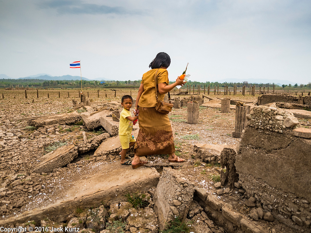 02 APRIL 2016 - NA SAK, LAMPANG, THAILAND:  A woman leads her son into the ruins of the Buddhist temple in Sobjant village. The village of Sobjant in Na Sak district in Lampang province was submerged when the Mae Chang Reservoir was created in the 1980s. The village was relocated to higher ground a few kilometers from its original site. The drought gripping Thailand drained the reservoir and the foundations of the Buddhist temple in the original village became visible early in 2016. Thai families come down to the original village to pray in the ruins of the temple and look at what's left of the village. This is the first time in more than 30 years that this area has not been under two meters of water.     PHOTO BY JACK KURTZ