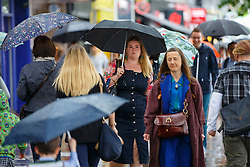 © Licensed to London News Pictures. 23/06/2016. London, UK. People take shelter from the rain underneath umbrellas in Islington, London on the polling day of the EU referendum on 23 June 2016. Photo credit: Tolga Akmen/LNP