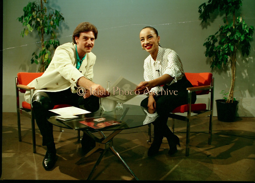 """Sade and Tony Hadley Interviews.  P92..1984.21.08.1984..08.21.1984..21st August 1984..As part of his interview sessions for """"Video File"""" for R.T.E., Marty Whelan interviewed international music stars. The interviews were held in the R.T.E.,studios and at various hotels throughout the city...Marty Whelan is pictured with Sade in the R.T.E.,studios in Donnybrook for her interview for """"Video Files""""."""