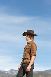 cowboy in a flannel shirt looking at a mountain range