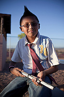 A young Navajo Indian boy with a mohawk and wearing a tie.  On the Navajo reservation in Chinle, Arizona