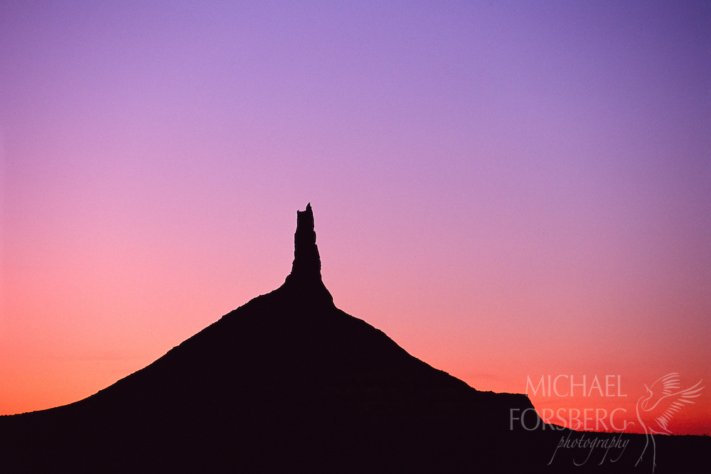 The silhouette of Chimney Rock cuts sharply across the purple and pink sky as the sun sets.  Western Nebraska.