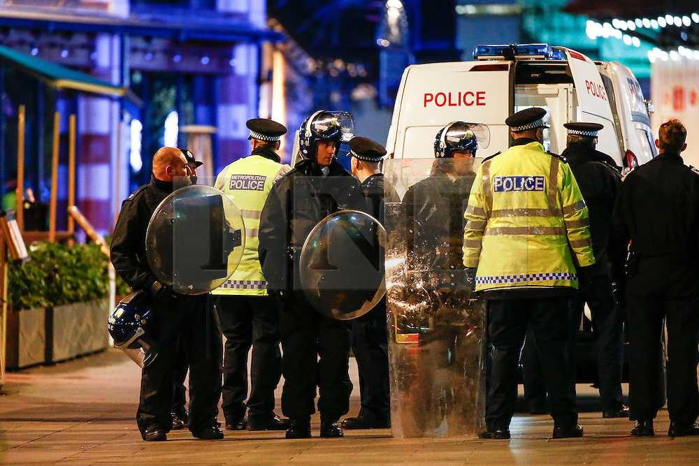 "© Licensed to London News Pictures. 24/02/2016. London, UK. Police in riot gear form a screen as a man is placed in to a van at the scene of a ""hostage situation"" at Bella Italia restaurant in Leicester Square, London where a man claiming to be in possession of a knife is holding a woman against her will. Metropolitan Police reported the incident is not terrorist-related. Photo credit: Tolga Akmen/LNP"