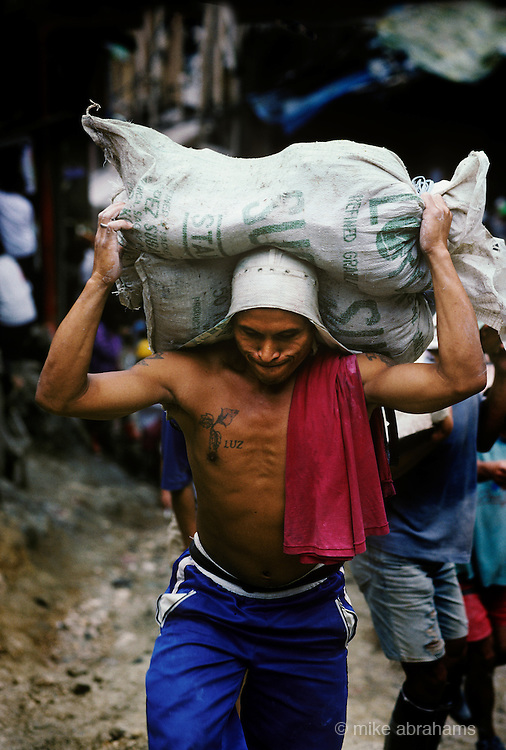 An abantero, a miner,  carrying a two 60 kg sacks of gold ore to the ballmills for processing into gold.. Mount Diwata, Mindanao, The Philippines