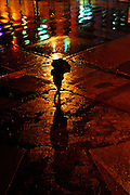 A woman walks along a rain-soaked Belleville, Ontario street.