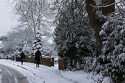© Licensed to London News Pictures. 21/01/2013, London, UK. People walk down a snow covered street in Croydon, South London, Monday, Jan. 21, 2013. Britain is continue affect by cold weather and snow. Photo credit : Sang Tan/LNP