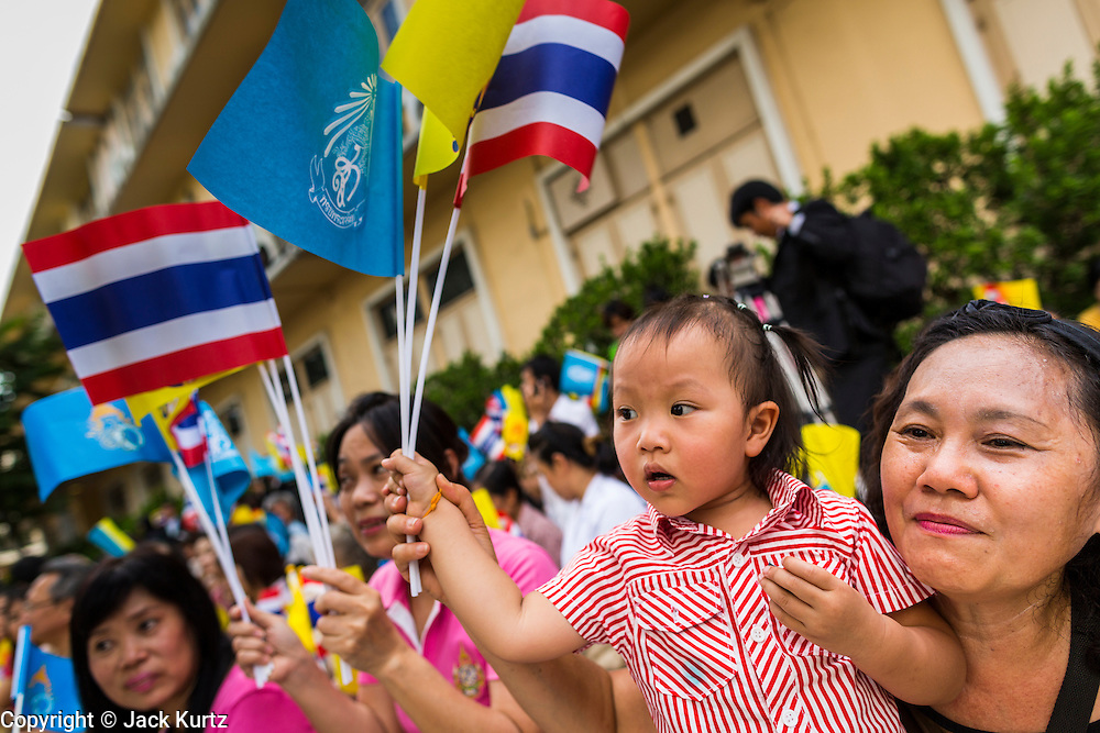 """01 AUGUST 2013 - BANGKOK, THAILAND: A Thai woman and her daughter wave the yellow flag of the monarchy while they chant """"Long Live the King"""" at Siriraj Hospital before Bhumibol Adulyadej, the King of Thailand, 85, was discharged from Bangkok's Siriraj Hospital, Thursday where he has lived since September 2009. He traveled to his residence in the seaside town of Hua Hin, about two hours drive south of Bangkok, with his wife, 80-year-old Queen Sirikit, who has also been treated in the hospital for a year.      PHOTO BY JACK KURTZ"""