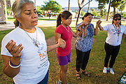 18 JUNE 2012 - PHOENIX, AZ: PETRA FALCONE, from PAZ, joins hands with others and prays that the US Supreme Court will overturn SB1070 Monday. About 20 people, members of the immigrant rights' group Promise AZ (PAZ) held a prayer vigil at the Arizona State Capitol in Phoenix Monday praying that the US Supreme Court would overturn SB 1070, Arizona's controversial anti-immigrant law. The court's ruling had been expected Monday, June 18 but the the court said the ruling would not come out until later this month. Members of PAZ said they would continue their vigil until the ruling was issued.      PHOTO BY JACK KURTZ