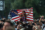 Bottles of water are thrown and a US flag is held up for the 4th July - Wireless festival, Finsbury Park, London, UK