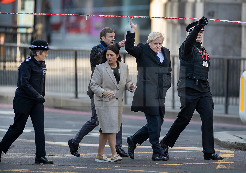 © Licensed to London News Pictures. 30/11/2019. London, UK. Prime Minister Boris Johnson visits the scene of the  London Bridge terrorist attack with (L-R) Commissioner of the Metropolitan Police Cressida Dick, Home Secretary Priti Patel and Commissioner of City of London Police Ian Dyson. Two people were killed and three injured after the attacker, named by police as 28-year-old Usman Khan stabbed a man and a woman to death on London Bridge. Photo credit: Peter Macdiarmid/LNP