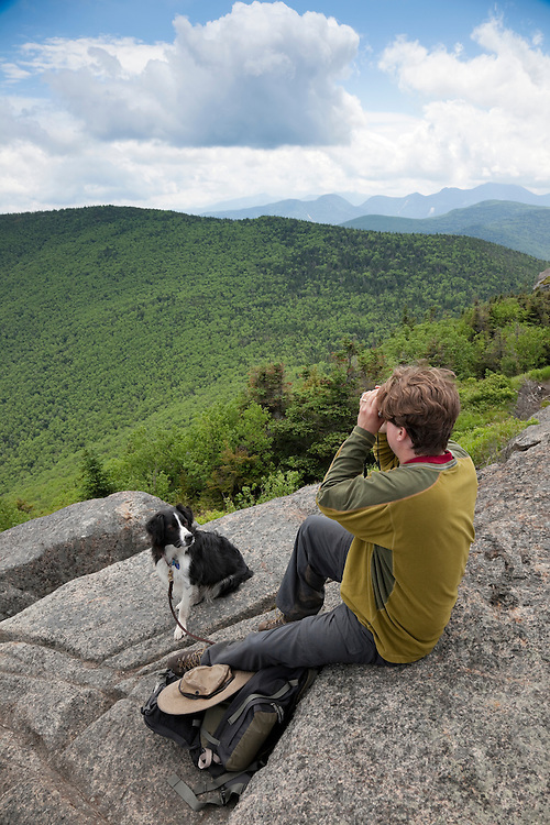 Man looking through binoculars with dog