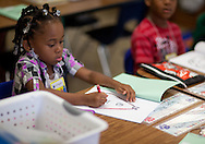 A'Tayjah Phillips, 5, kindergarten, of Cedar Rapids, works on coloring on the first day of school at Polk Elementary School, 1500 B Avenue NE, in Cedar Rapids on Thursday morning, July 21, 2011.