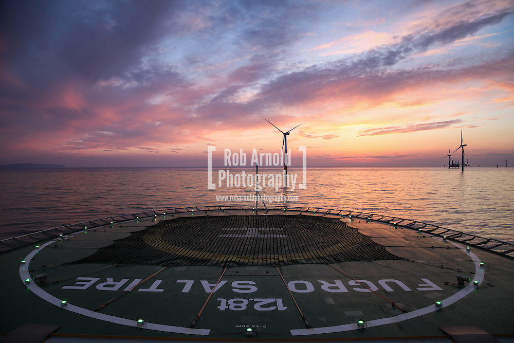 © Rob Arnold.  16/04/2014. North Wales, UK. Sunset aboard the cable trenching vessel, MV Fugro Saltire, on the Gwynt y Môr Offshore Wind Farm off the coast of North Wales. Photo by Rob Arnold