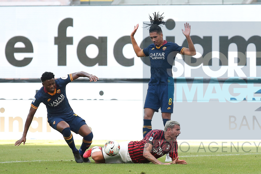 AC Milan's French defender Theo Hernandez is upended in the box by AS Roma's English defender Chris Smalling conceding a penalty as AS Roma's Guinean midfielder Amadou Diawara looks on during the Serie A match at Giuseppe Meazza, Milan. Picture date: 28th June 2020. Picture credit should read: Jonathan Moscrop/Sportimage