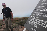 John Walcott rounds the corner and gets a look at the sign at the summit of Mt Katahdin in Maine's Baxter Peak.  Katahdin is the highest point in Maine and is the northern terminus of the Appalachian Trail, which extends 2175 miles south to Springer Mountain in Georgia.  Walcott first climbed Katahdin in 1976 and has been returning almost yearly.  In 2010 he celebrated his 60th birthday on the summit.