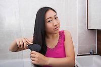 Portrait of Asian woman brushing her hair in bathroom