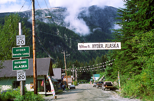 main street businesses; Welcome sign; rustic small town; mountain scenery; Hyder; AK; Alaska