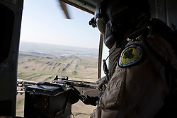 © Licensed to London News Pictures. 11/12/2014. Fishkhabour, Iraq. The door gunner of an Iraqi Air Force Mi-17 Hip helicopter keeps watch during a mission to resupply peshmerga, PKK and Yazidi refugees trapped on Mount Sinjar.<br /> <br /> Although a well publicised exodus of Yazidi refugees took place from Mount Sinjar in August 2014 many still remain on top of the 75 km long ridge-line, with estimates varying from 2000-8000 people, after a corridor kept open by Syrian-Kurdish YPG fighters collapsed during an Islamic State offensive. The mountain is now surrounded on all sides with winter closing in, the only chance of escape or supply being by Iraqi Air Force helicopters. Photo credit: Matt Cetti-Roberts/LNP