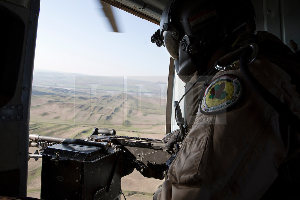 &copy; Licensed to London News Pictures. 11/12/2014. Fishkhabour, Iraq. The door gunner of an Iraqi Air Force Mi-17 Hip helicopter keeps watch during a mission to resupply peshmerga, PKK and Yazidi refugees trapped on Mount Sinjar.<br /> <br /> Although a well publicised exodus of Yazidi refugees took place from Mount Sinjar in August 2014 many still remain on top of the 75 km long ridge-line, with estimates varying from 2000-8000 people, after a corridor kept open by Syrian-Kurdish YPG fighters collapsed during an Islamic State offensive. The mountain is now surrounded on all sides with winter closing in, the only chance of escape or supply being by Iraqi Air Force helicopters. Photo credit: Matt Cetti-Roberts/LNP