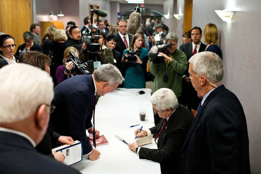 Republican presidential candidate Newt Gingrich signs copies of his book after addressing the Polk County Republican Party's Robb Kelley Victory Club dinner on Thursday, December 1, 2011 in Johnston, IA.